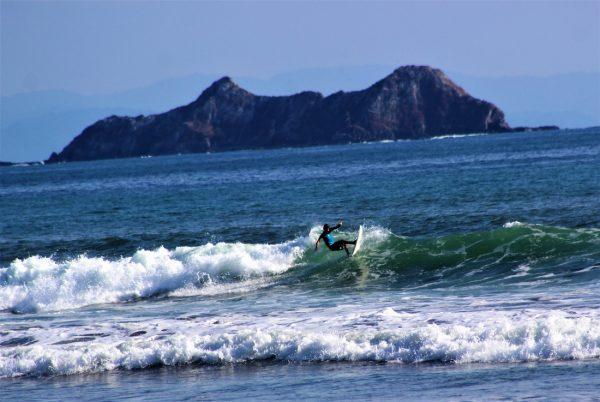 A surfer braves the waves off the coast of Uvita COSTA RICA